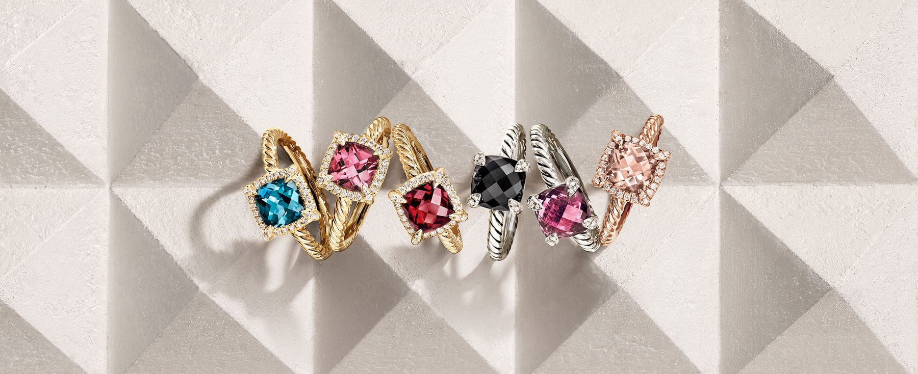 A color photograph shows an overhead shot of nine David Yurman women's rings in a horizontal stack atop a beige-hued stone surface with pyramid-shaped protrusions. The women's rings are crafted from 18K yellow gold with white diamonds and with or without rubies, a cultured pearl or garnet.