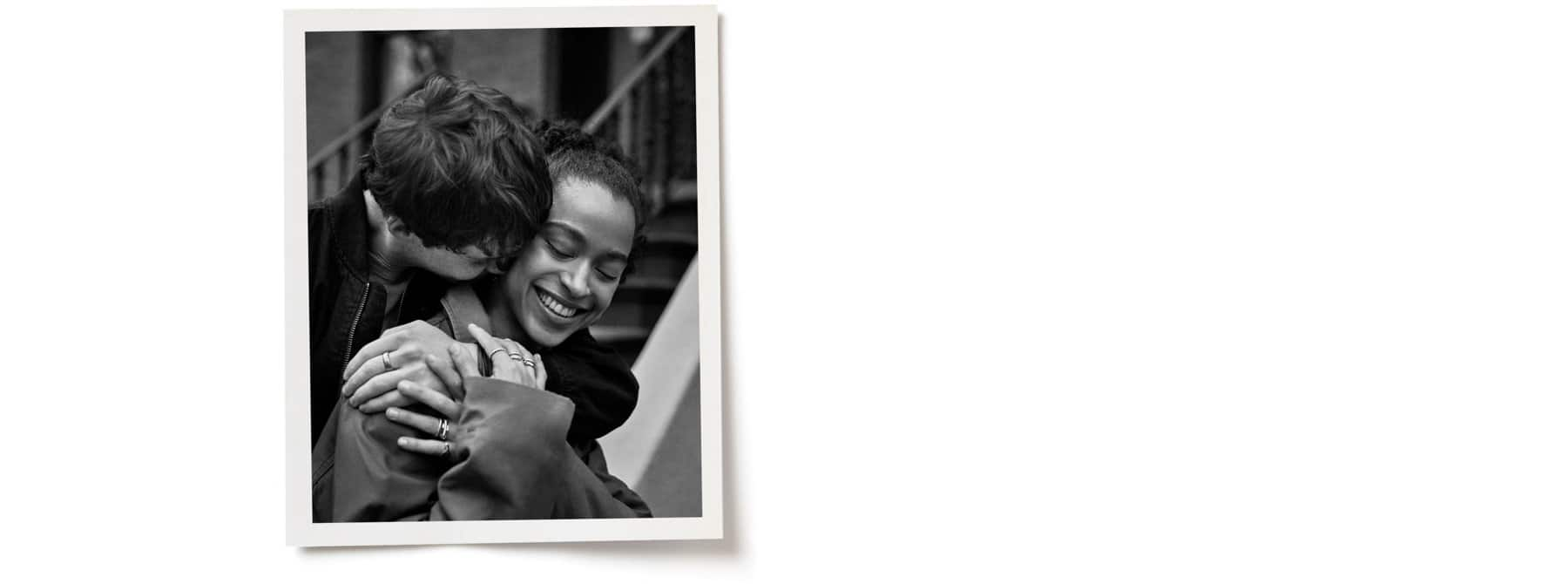 A black-and-white photo atop a white background depicts Josh behind a smiling Zora, with his head nuzzled in her shoulder. Both are wearing David Yurman jewelry.