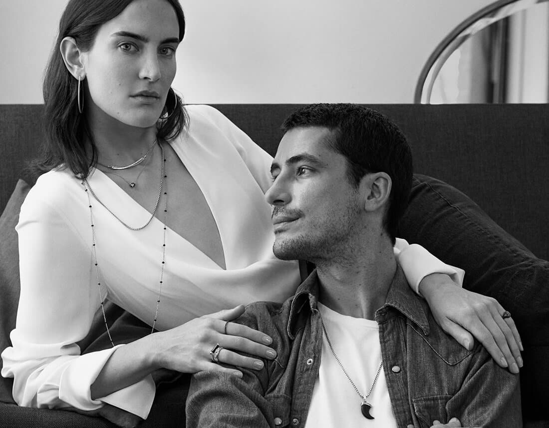 A black-and-white photo of Josh sitting on a couch with his arm around Zora. Both are wearing David Yurman jewelry.