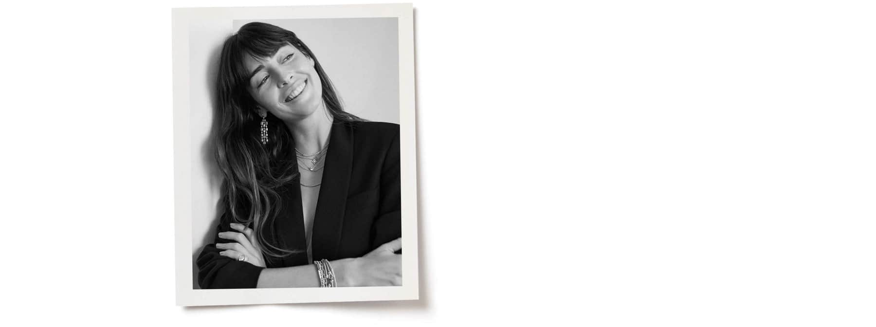 A black-and-white photo of Juliette is placed on top of a white background. The photo show Juliette smiling with her head tilted to the left while wearing David Yurman jewelry.