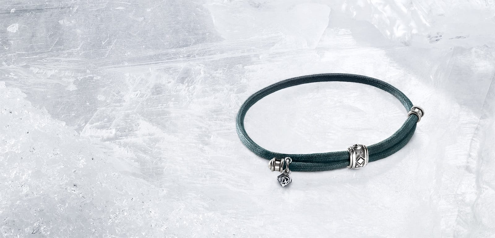 A David Yurman Renaissance waxed-cord bracelet in teal with chrome-plated details shot on a backdrop of ice.