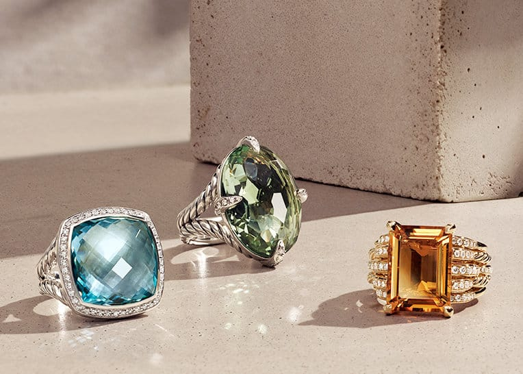 David Yurman Albion®, Châtelaine® and Tides rings in sterling silver with blue topaz or prasiolite and pavé diamonds, or in 18K yellow gold with citrine and pavé diamonds on a beige-colored stone with long shadows.