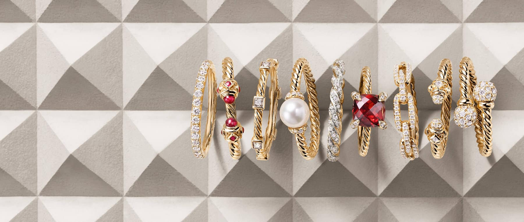 A color photo shows a horizontal stack of nine David Yurman women's rings from the DY Eden, Renaissance, DY Astor, Solari, Pavéflex, Châtelaine and Stax placed atop a beige-colored stone with pyramid-shaped protrusions. The women's jewelry is crafted from 18K yellow gold with or without white diamonds, rubies or garnet.
