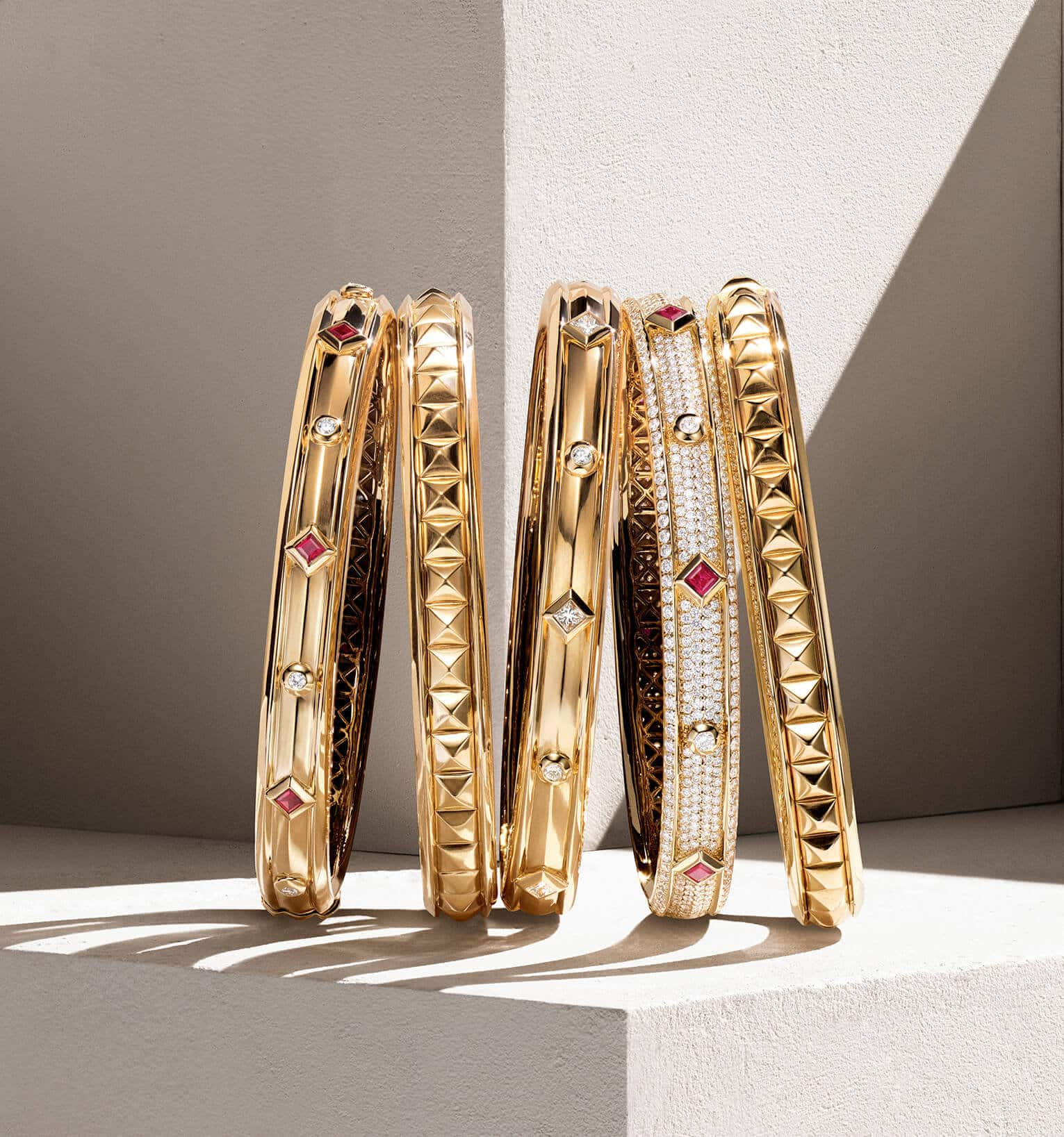 A color photo shows a horizontal stack of five David Yurman bracelets from the Modern Renaissance collection leaning against each other on top of a beige-hued stone shelf with hard diagonal shadows. The women's jewelry is crafted from 18K yellow gold with or without white diamonds and rubies.