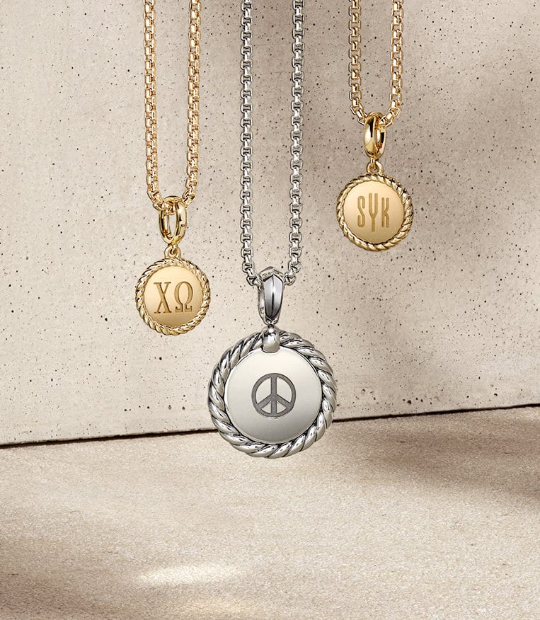 David Yurman Cable Collectibles® pendant necklaces in 18K yellow gold or sterling silver custom-engraved with the Greek letters Chi Omega, a peace symbol, or nothing, hanging above sand-colored stones and casting long shadows.