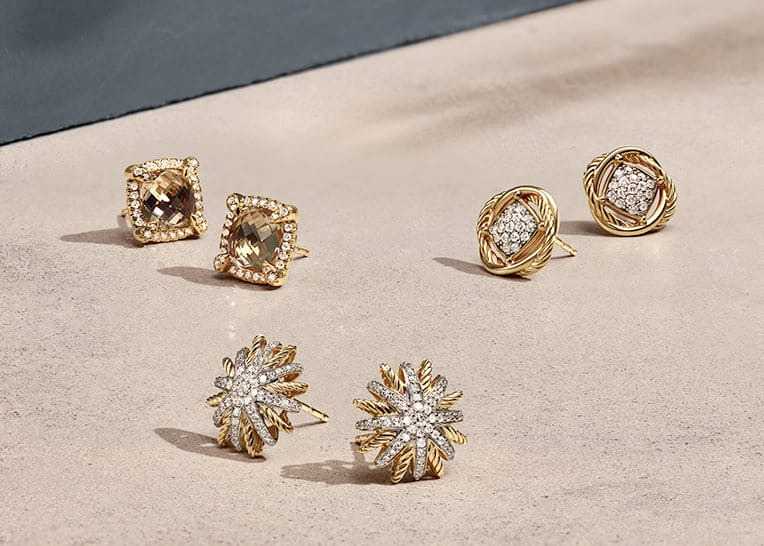 A color photo of three pairs of David Yurman stud earrings in 18K yellow gold with pavé diamonds and champagne-colored citrine, all scattered on top of a beige-colored stone background with shadows.