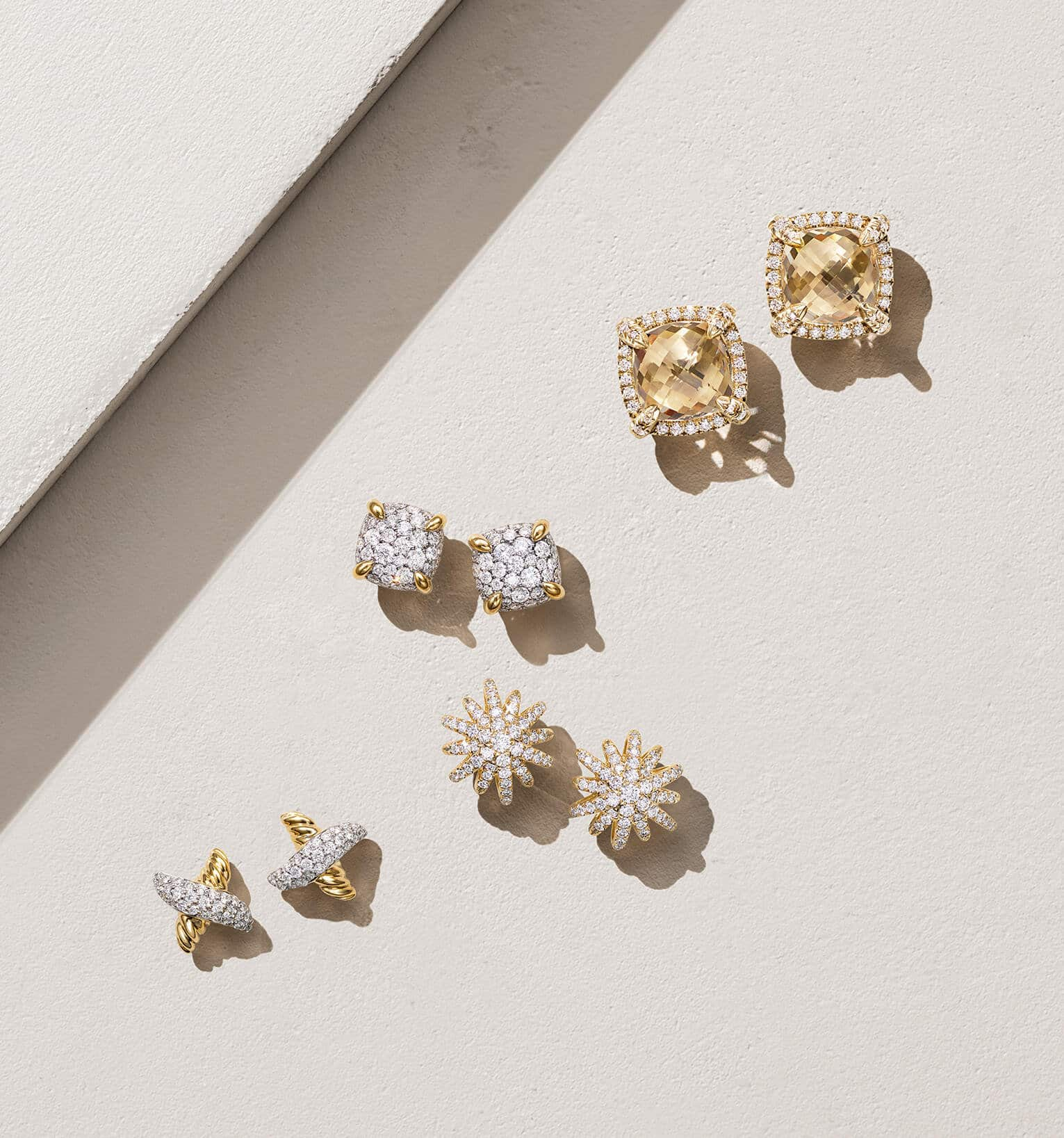 A color photograph shows an overhead shot of four pairs of David Yurman stud earrings for women from the X, Starburst and Châtelaine collections scattered atop a beige-hued stone shelf with hard diagonal shadows. The women's earrings are crafted from 18K yellow gold with pavé white diamonds and with or without Champagne citrine center stones.