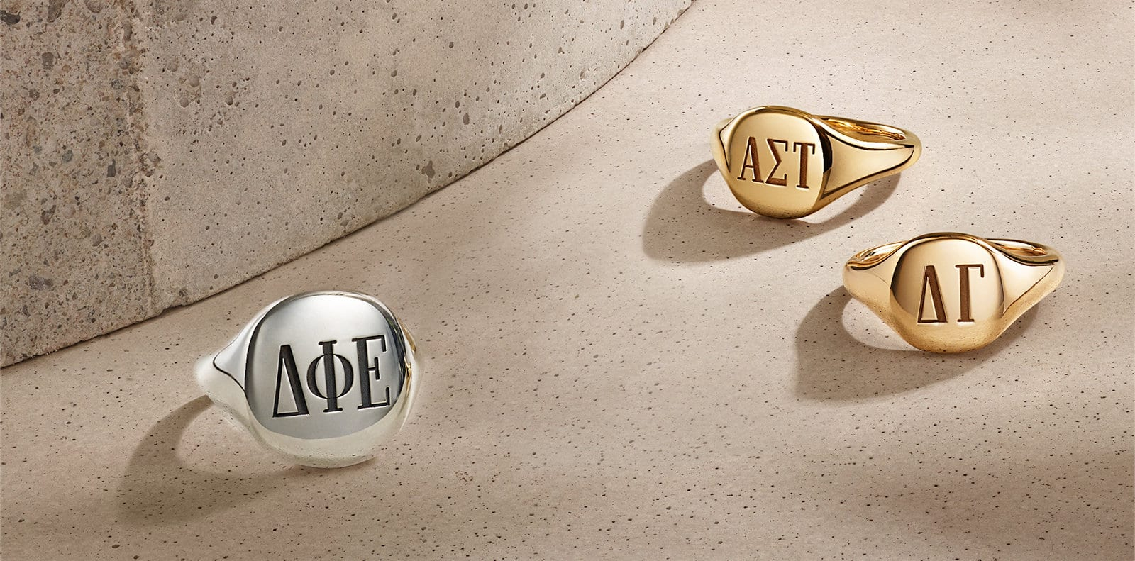 A color photo of three David Yurman Pinky Rings engraved with Greek letters, all scattered on top of a beige-colored stone background with shadows. Two rings are in 18K yellow gold and one is in sterling silver.