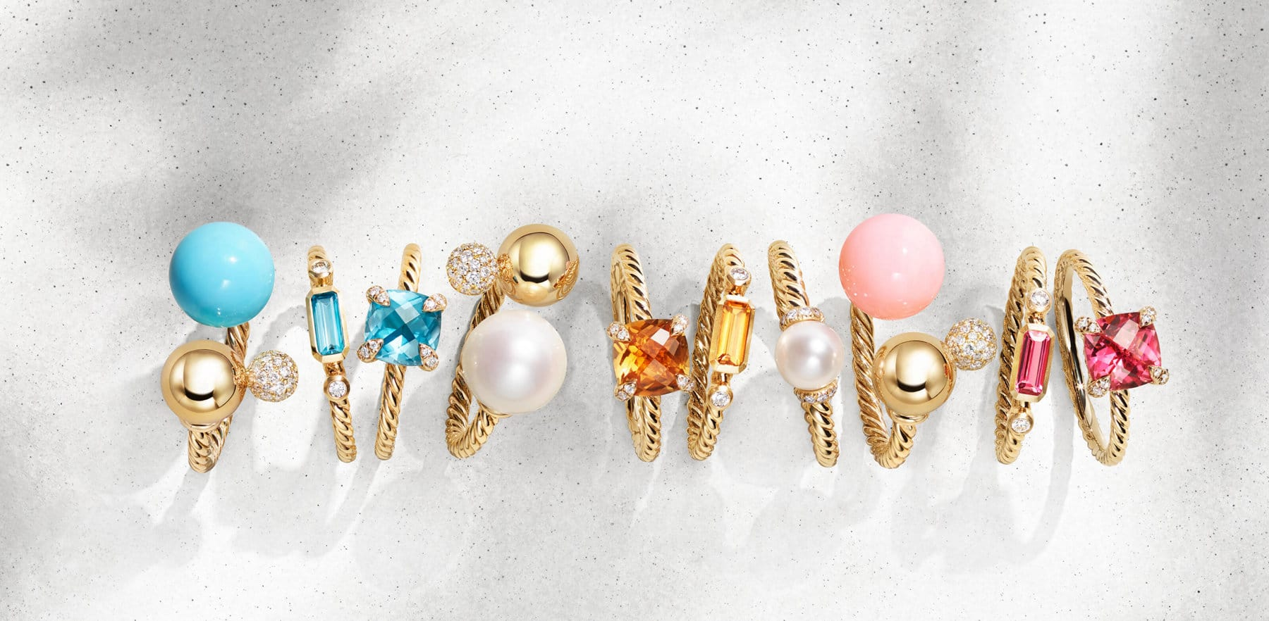 A chromatic horizontal stack of David Yurman Chatelaine, Novella and Solari rings in 18K yellow gold with white diamonds and a variety of colored gemstones, standing on top of and casting long shadows on a white textured stone. This photo is contrasted with a collage of a gold chains hanging over a white background near large colored gemstones including pearls, gold balls and pink moonstone.