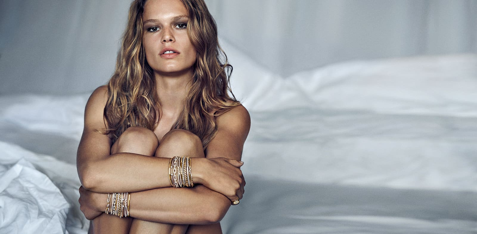 Model Anna Ewers wearing multiple David Yurman Continuance®, Stax and CableSpira bracelets in 18K yellow gold with pavé diamonds on a bed.