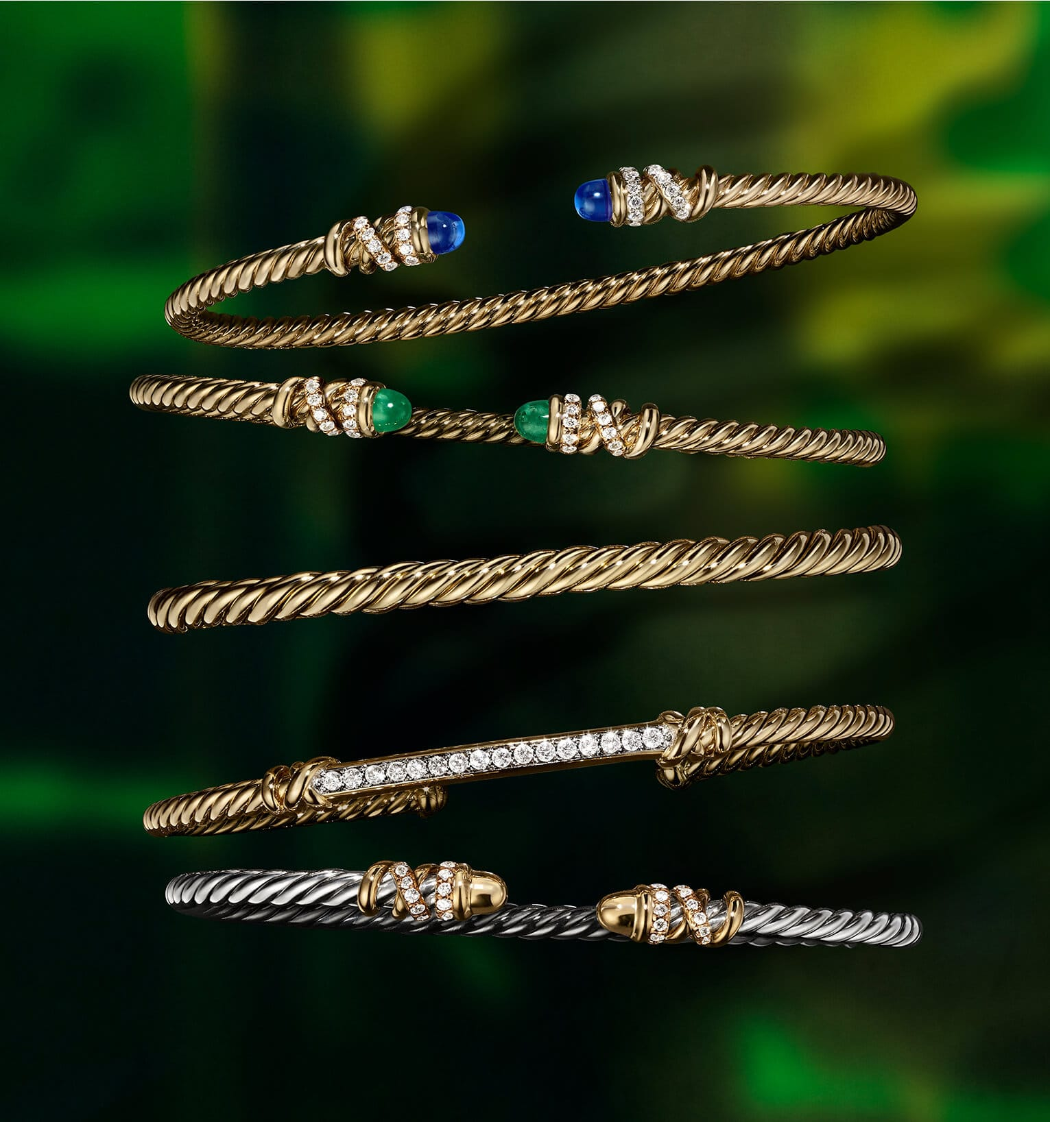 A color photograph shows an overhead shot of a horizontal stack of five David Yurman bracelets from the Helena and Cablespira collections placed atop a dark green surface with illuminated sections. The women's jewelry is crafted from 18K yellow gold or mixed metals with pavé white diamonds and emerald, gold or tanzanite end caps.