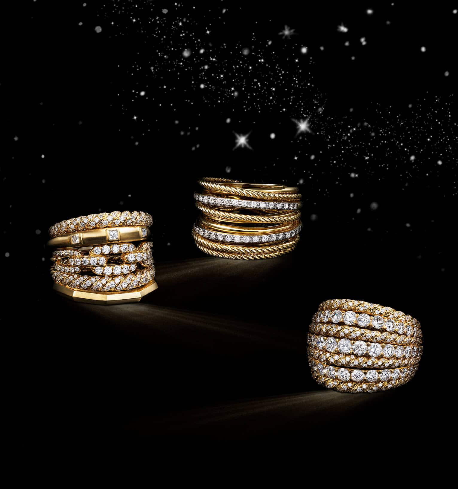 A color photo shows three David Yurman women's rings from the Stax, Crossover and High Jewelry collections floating in front of a starry night sky. The jewelry is crafted from 18K yellow gold with pavé diamonds.