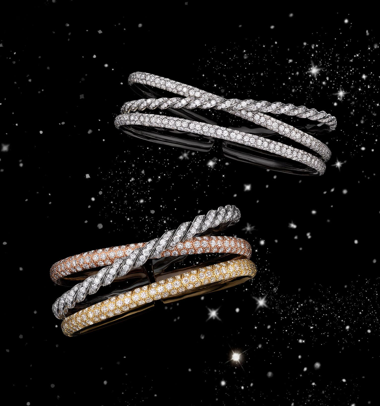 A color photo shows two David Yurman Pavéflex three-row bracelets floating in front of a starry night sky. One bracelet is crafted from 18K white gold with pavé diamonds while the other is crafted from 18K yellow, white and rose gold with pavé diamonds.
