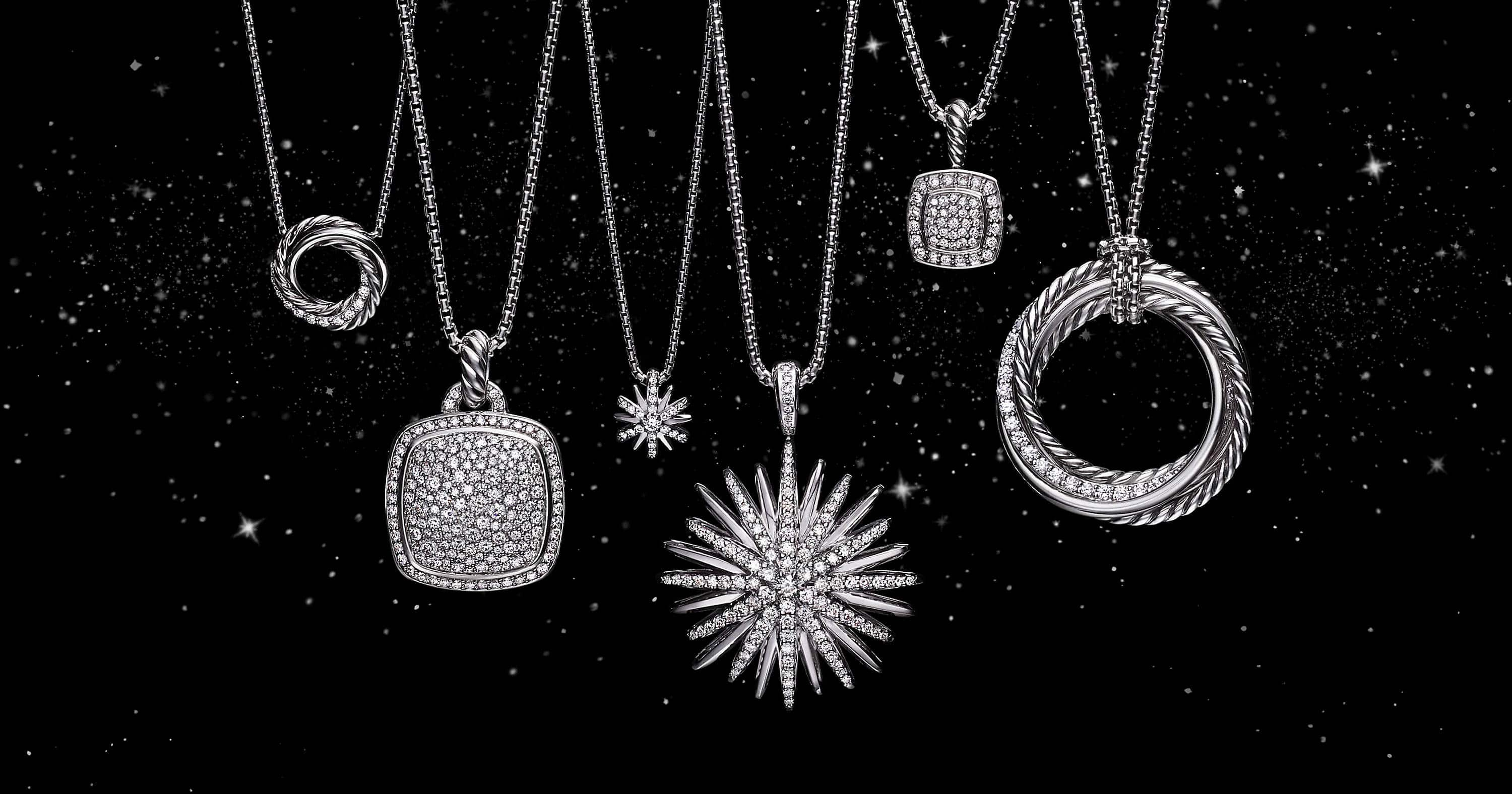 A color photo shows a horizontal row of six David Yurman pendant necklaces hanging in front of a starry night sky. The women's jewelry is crafted from 18K white gold or sterling silver with pavé diamonds. The pendants are shaped like stars, twisted circles of Cable or a cushion-cut stone.
