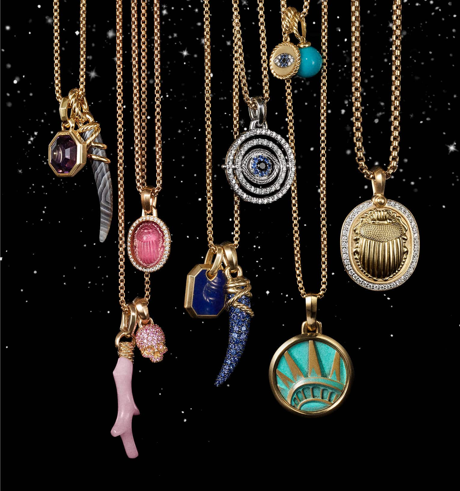 A color photograph shows 10 David Yurman amulet pendants hanging from a horizontal row of chain necklaces in front of a starry night sky. The women's jewelry is crafted from 18K yellow gold or sterling silver with or without pavé diamonds and an array of colored gemstones. The pendants come in various shapes such as a branch of coral, horn, dagger, or skull or depict a multitude of images such as a scarab and the Statue of Liberty's crown.