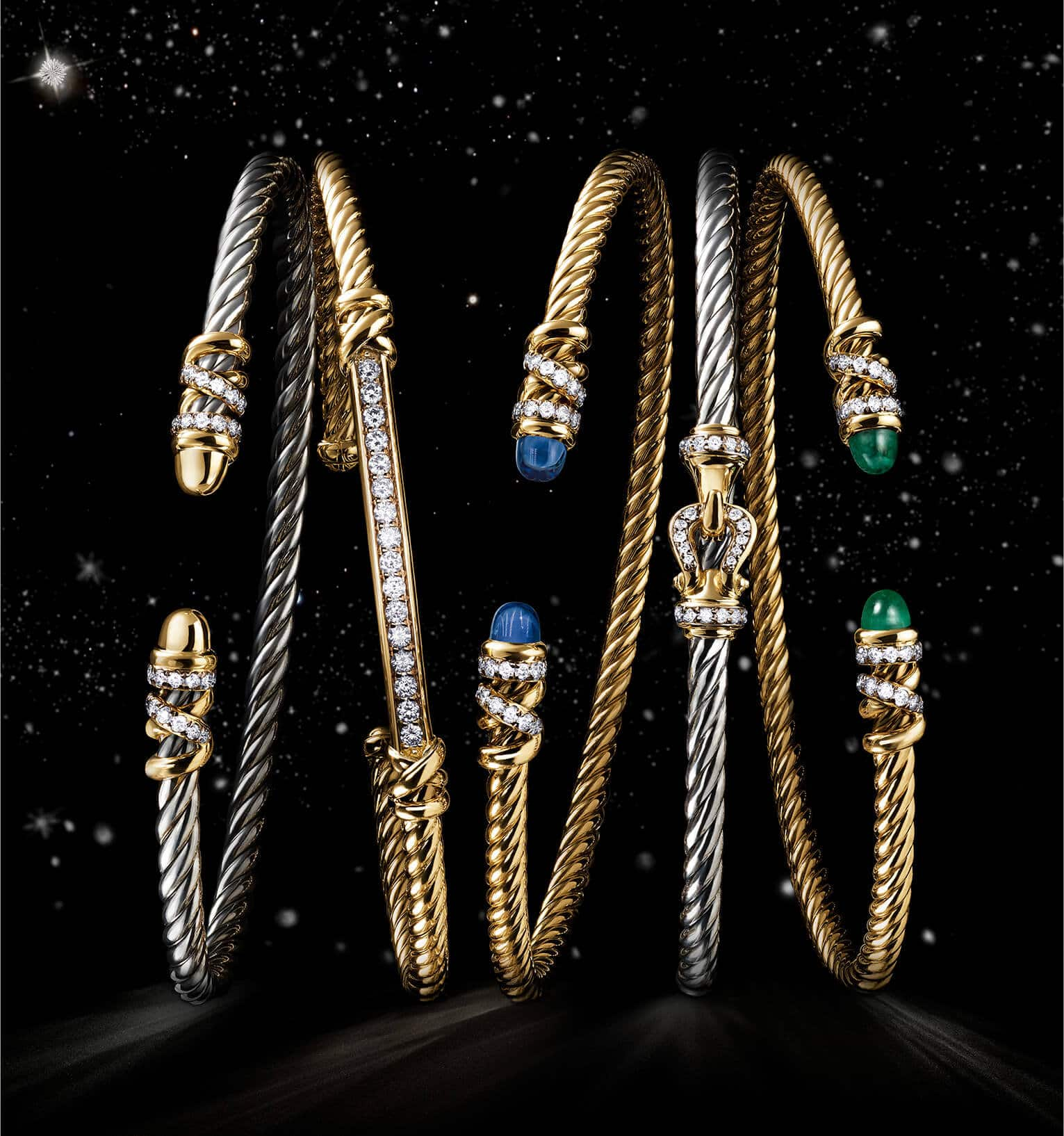 A color photo shows an overhead shot of a horizontal stack of five David Yurman bracelets from the Helena and Buckle collections floating in a starry night sky. Three of the women's bracelets are crafted from 18K yellow gold with pavé diamond, emerald or tanzanite accents. Two of the women's bracelets are crafted from sterling silver with 18K yellow gold and pavé diamond accents.