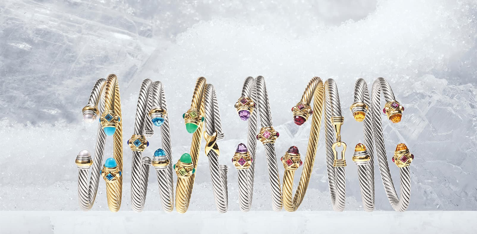 The Cable Collection® bracelets in sterling silver, 18K yellow gold and several colorful gemstones, in a row on sheets of ice.