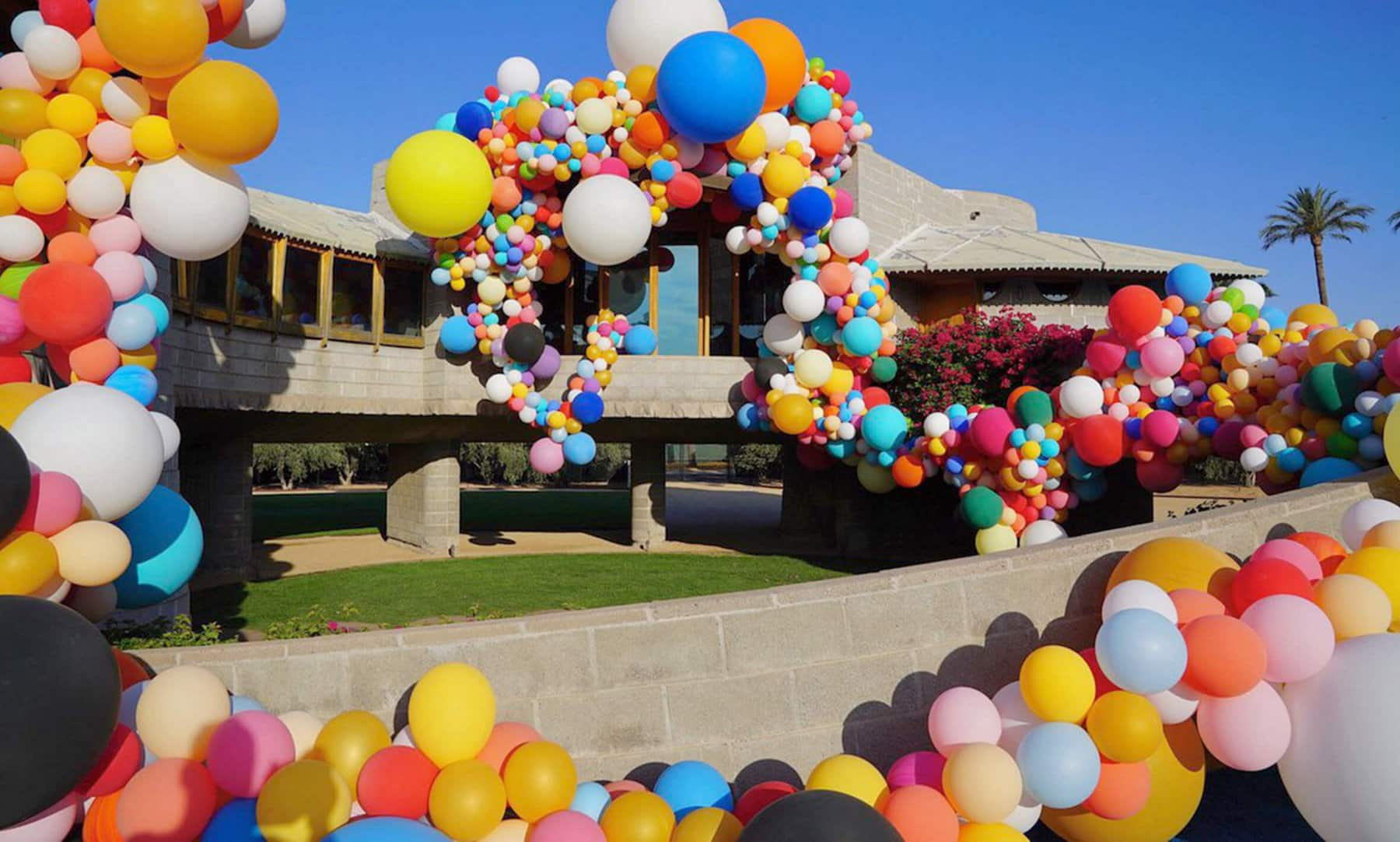 A color photo of vibrant balloons in various shades and sizes adorning the Frank Lloyd Wright house in Phoenix.