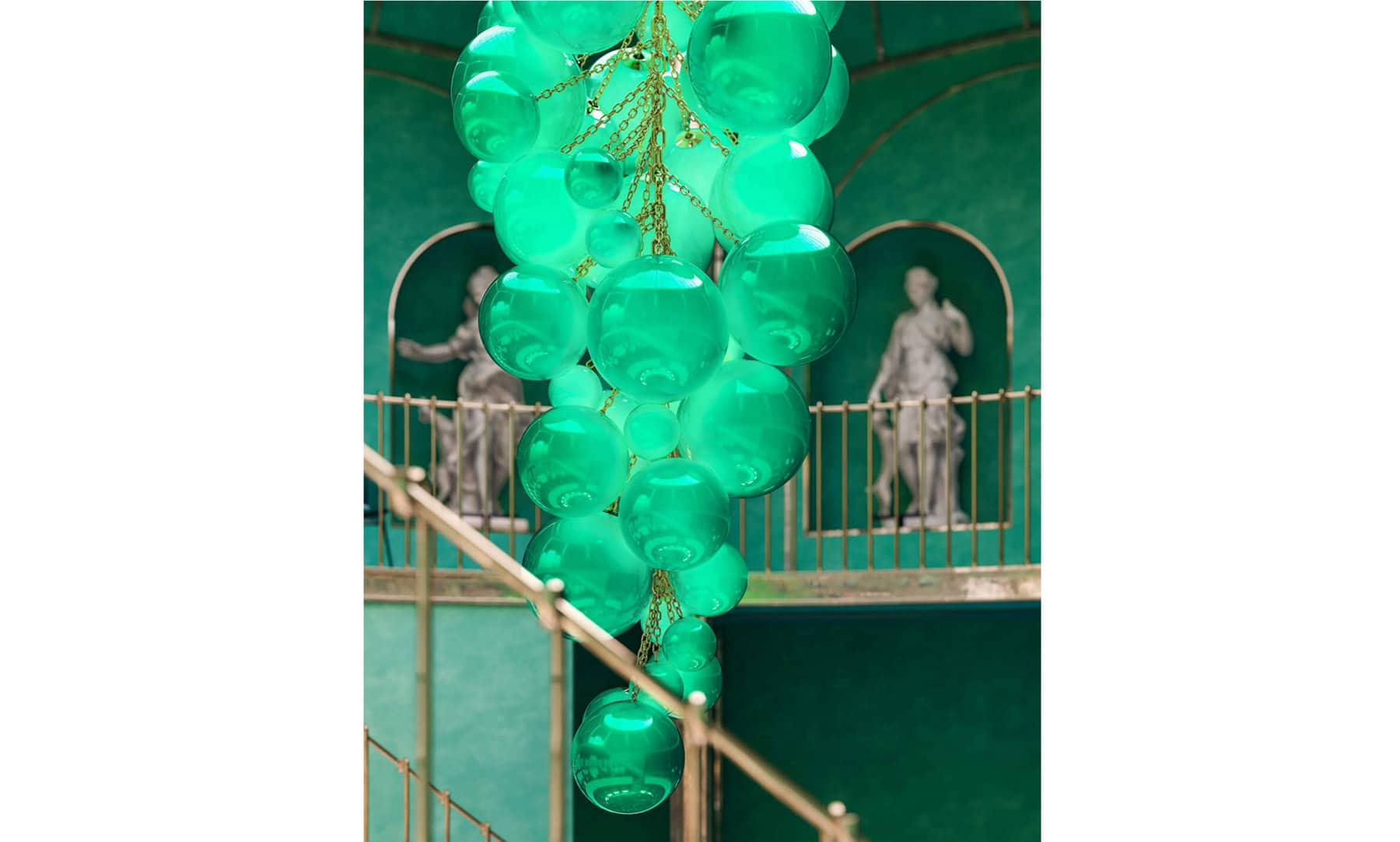 A color photo of a large, sculptural chandelier consisting of green orbs in various sizes, hanging in a green hall with light grey stone statues in the background.