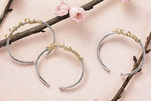 "David Yurman DY Whispers bracelets in sterling silver with gold wire scripted to say ""I love you"" in English, French or Spanish, arranged around dark branches blooming with cherry blossoms on top of a light pink stone."