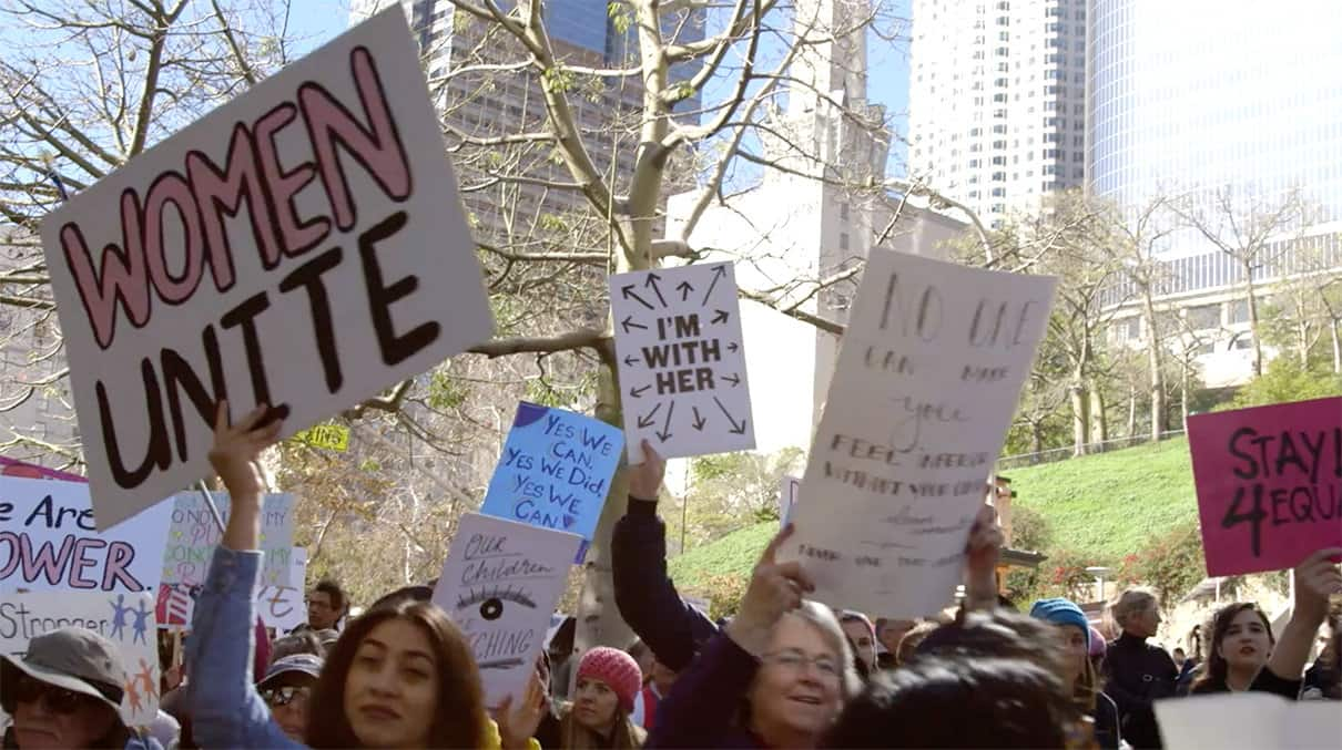 "A still from the documentary ""This Changes Everything"" shows a group of female protestors holding signs saysing ""Women Unite"" and ""I'm With Her"" at the 2017 Women's March. The protestors are gathered in front of city buildings."