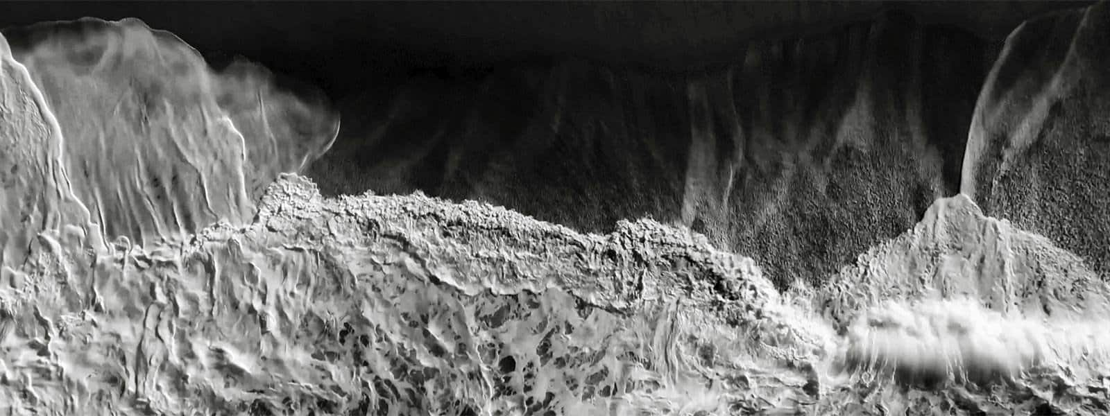 A black-and-white photo of ocean tides crashing on the sand.