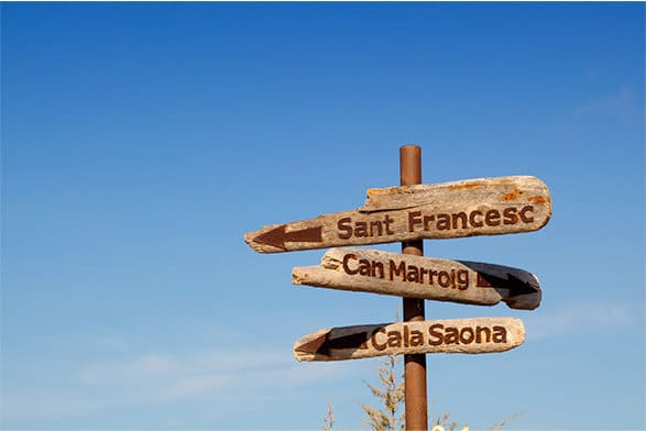 A color photo of a wooden sign pointing the way to Sant Francesc, Cala Saona and Can Marroig.