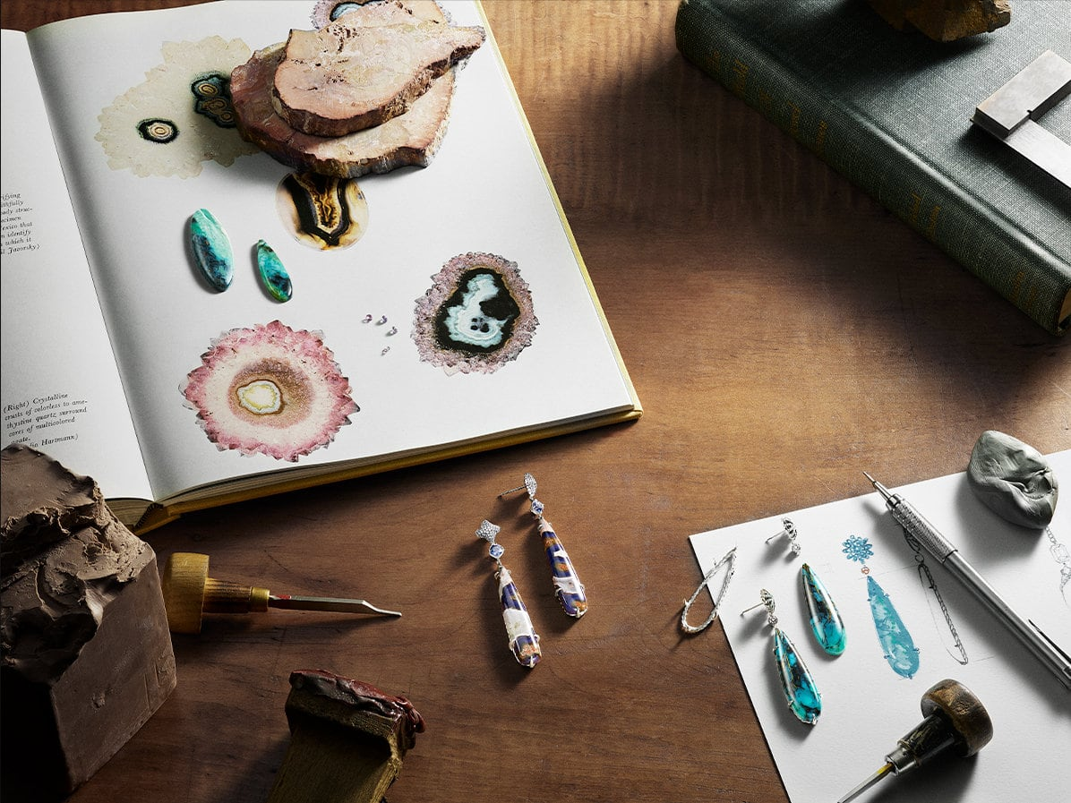 A sketchbook open with turquoise cabochons next to illustrations of different types of gemstones and David Yurman earrings with purple sapphires and passion agate on a wooden table. Jewelers' tools sit atop the table along with a gouache of David Yurman earrings with David Yurman blue opalized wood earrings on top of the paper and sterling silver earring setting.