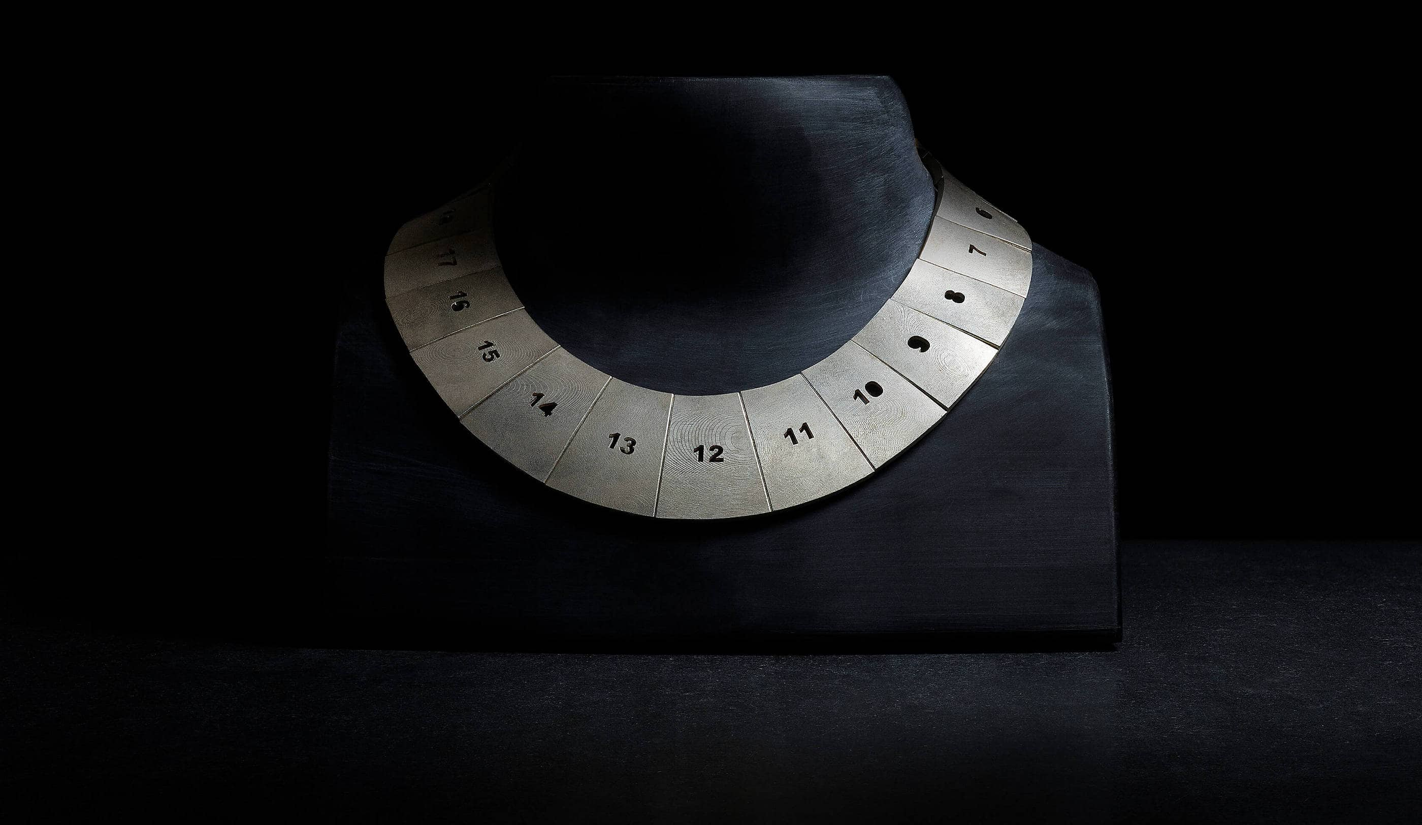 A image of a black neck form with a numbered metal necklace design.