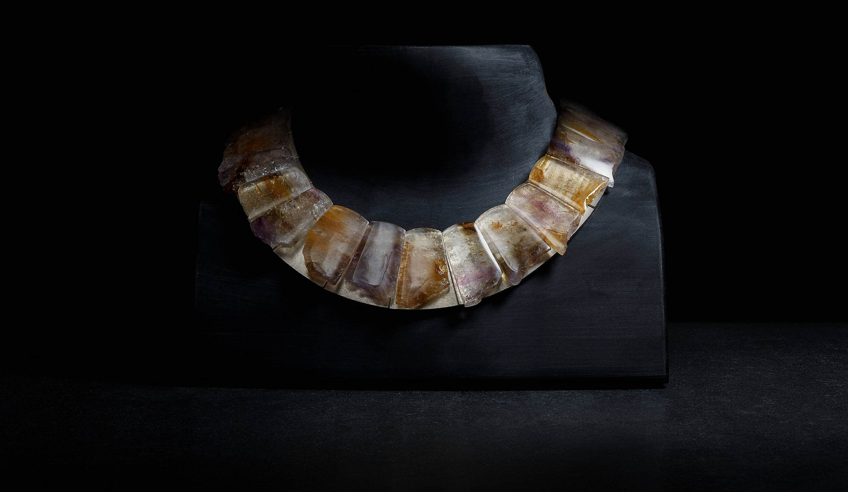 A image of a black neck form with a necklace design covered with pieces of cacoxenite.