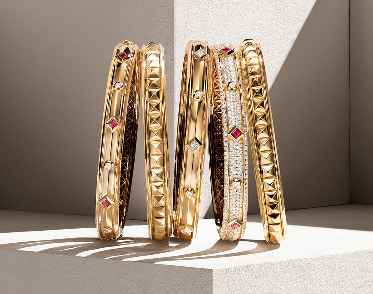 A color photo shows a horizontal stack of five David Yurman women's 18K yellow gold bracelets from the Renaissance Collection standing upright in front of a beige stone background partially covered with a diagonal shadow and on top of a beige stone surface, casting long shadows. The designs are crafted from 18K yellow gold with or without diamond-shaped rubies and diamonds.