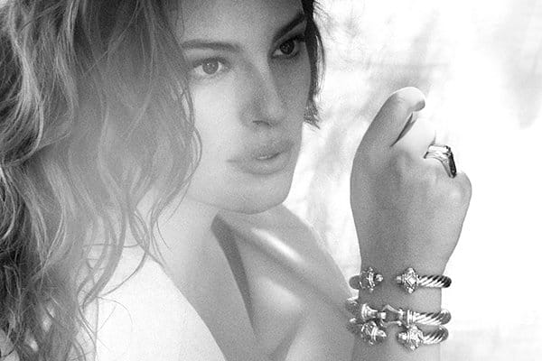 A black-and-white photograph of model Ashley Graham with one hand near her face while wearing a trench coat, two David Yurman Renaissance bracelets and a buckle bracelet on her wrist.