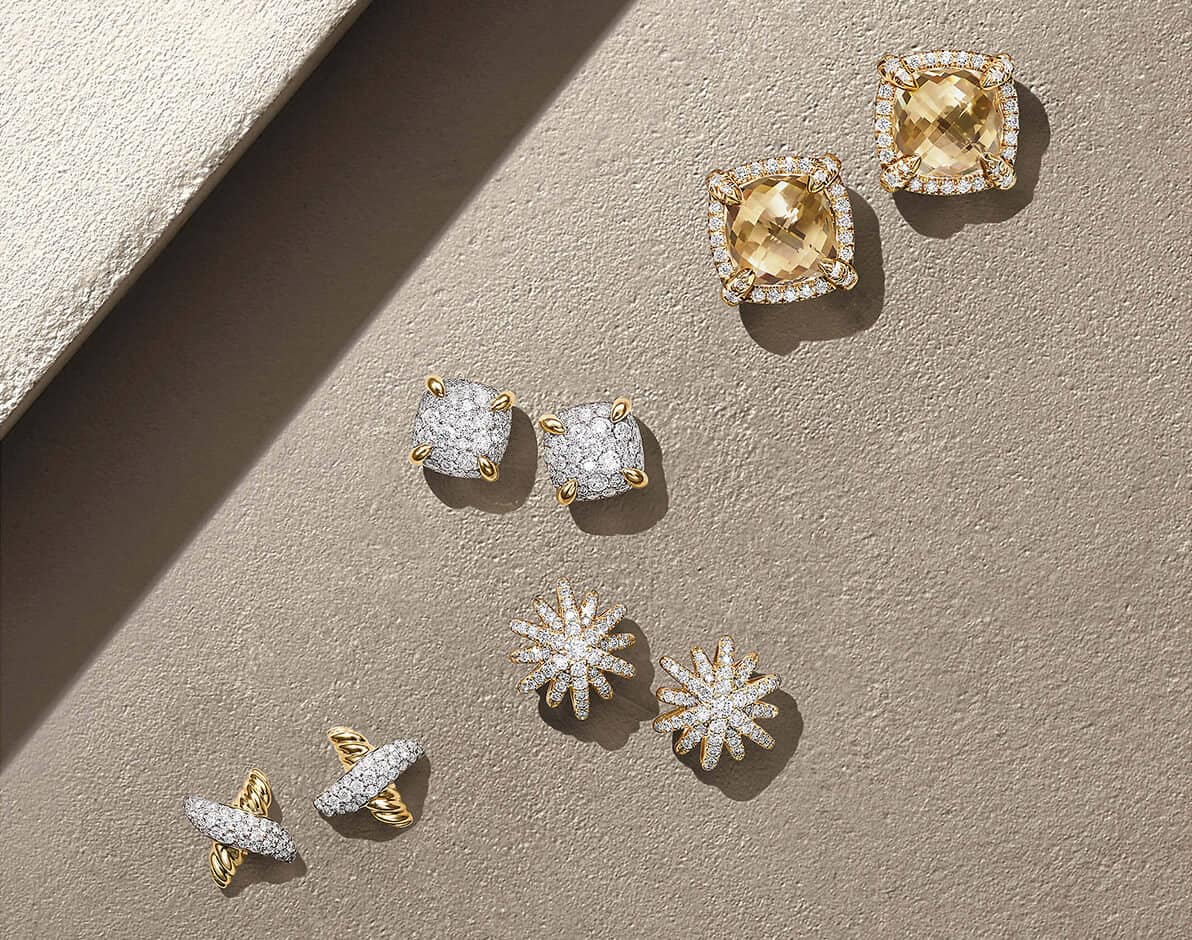 A color photograph shows four 18K yellow gold pairs of David Yurman women's pavé diamond stud earrings placed in a diagonal row on a beige stone with a diagonal ray of light. From left is a Petite Pavé X pair, a Starburst pair and two Châtelaine pairs with or without Champagne citrine center stones.