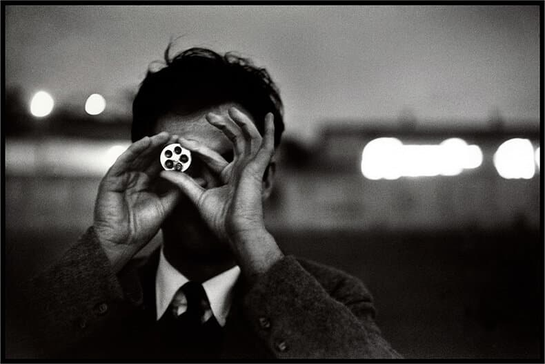 A black-and-white image shows photographer Ernst Haas holding a camera instrument in his hands in front of his face in front of a cityscape.