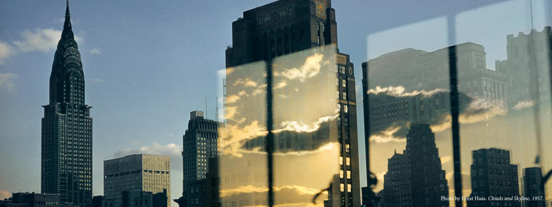 A color photo by Ernst Haas abstracts light reflections and clouds with the New York City skyline. A photograph of the Chrysler Building and midtown Manhattan is juxtaposed with four long rectangles showing a golden-and-blue sky with white clouds above the Manhattan skyline.