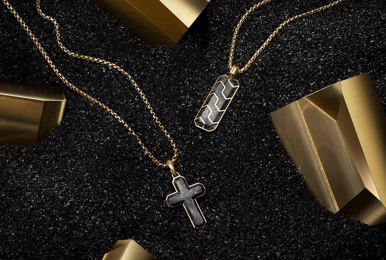 David Yurman Forged Carbon cross and ingot tags, in 18K gold with forged carbon, are strung on 18K gold chains and lay near blocks of gold in a pile of forged carbon shavings.