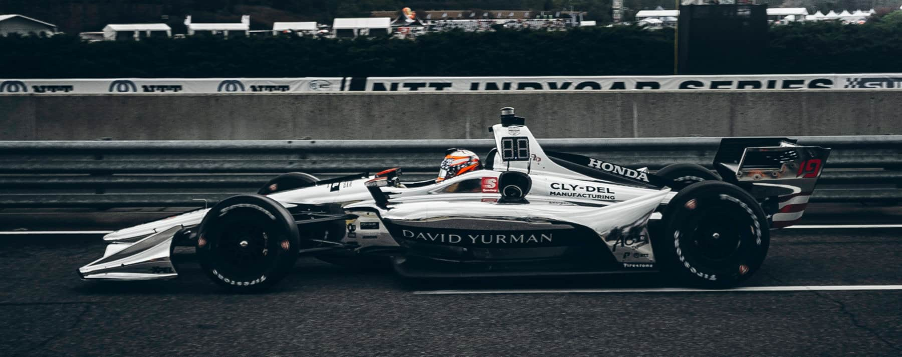 "A color photo of Santino Ferrucci driving his #19 IndyCar with ""David Yurman"" trim down a grey track."