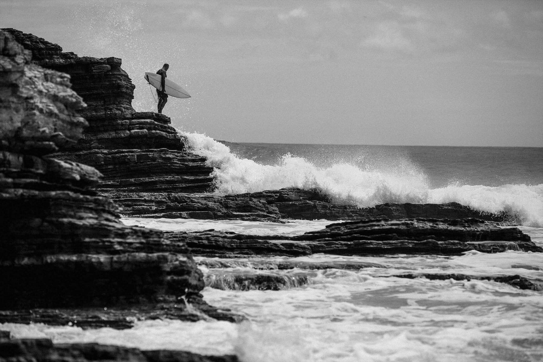 A black-and-white photo shows Jeff Johnson standing on a rocky shoreline holding a surfboard while looking down at the pounding surf.
