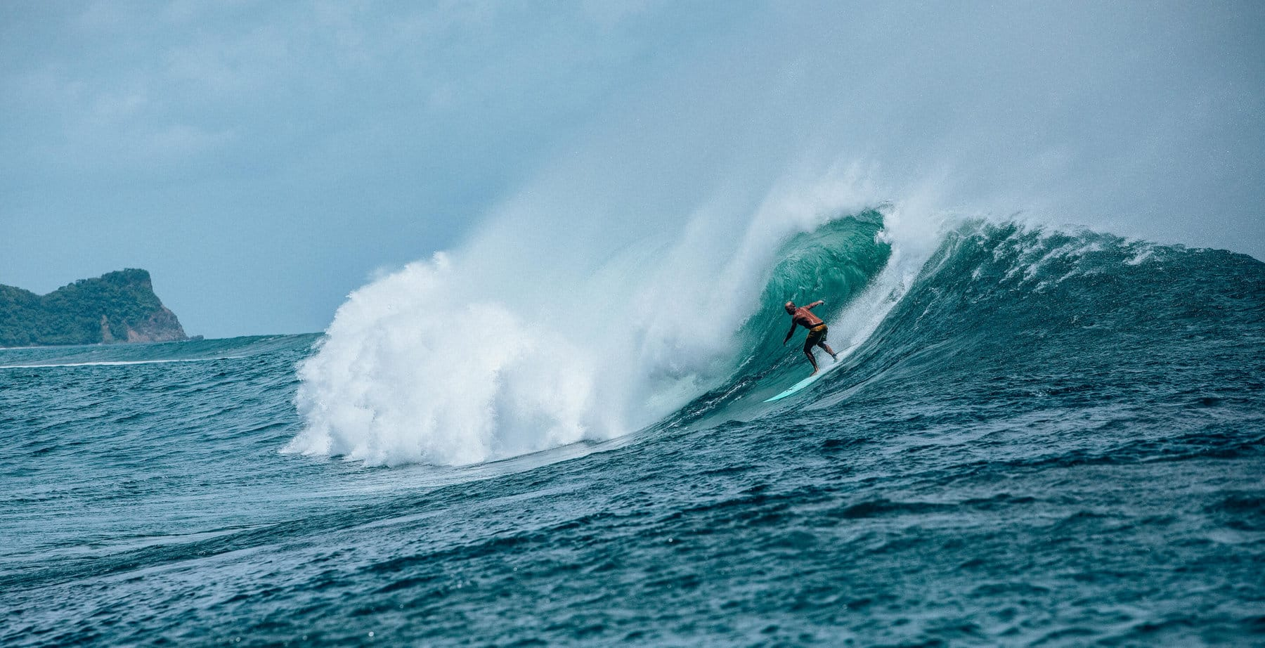 A color photo shows Jeff Johnson wearing board shorts and surfing a large wave in Nicaragua.