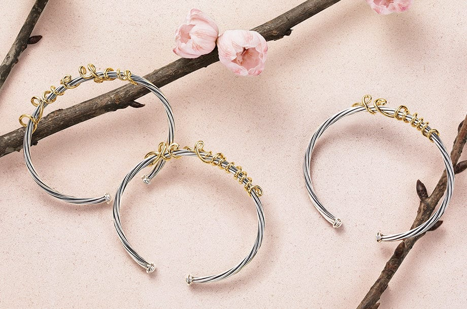 "A still from an animation showing a David Yurman DY Whispers bracelet with gold wire scripted to say ""I love you"" positioned over a branch with cherry blossoms."