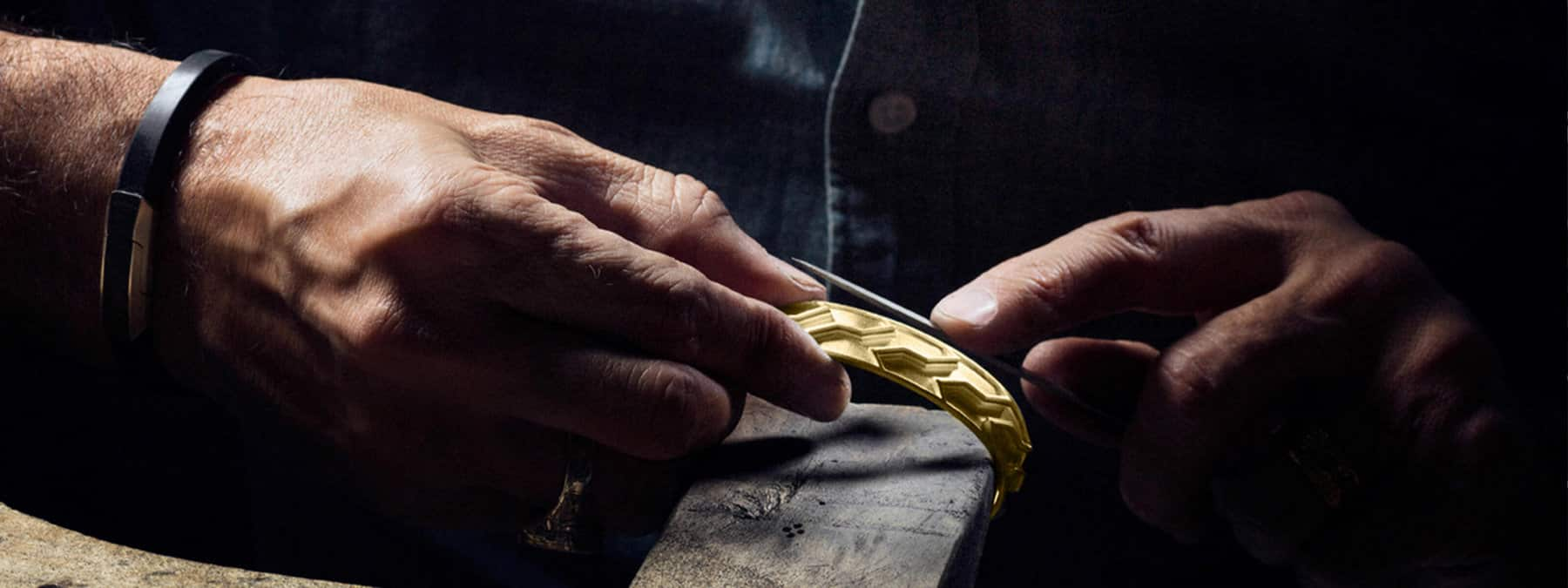 A color photo of a master craftsman's hands finishing an 18K gold cast of a Forged Carbon cuff bracelet on a well-worn jeweler's bench.