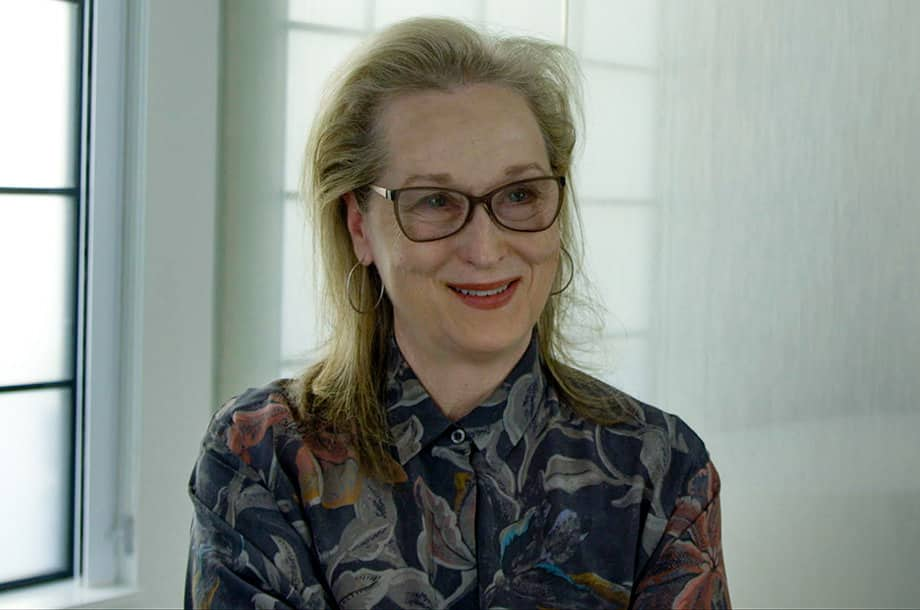 "A film still from ""This Changes Everything"" shows actress Meryl Streep smiling in front of a white wall and window. She wears a dark floral shirt and glasses."