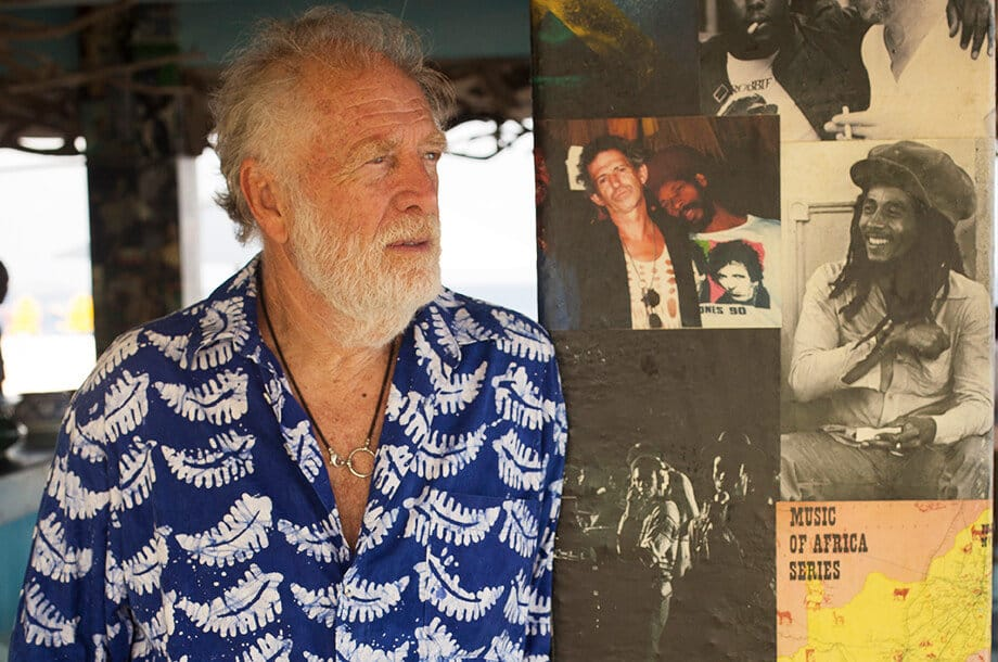Photo en couleur de Chris Blackwell à côté d'un mur de photos de Bob Marley.