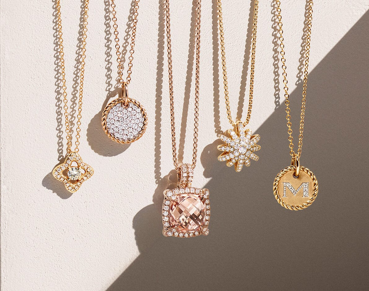 "A color photo shows five David Yurman women's pavé diamond pendant necklaces hanging in a horizontal row in front of a block of textured beige stone partially covered with a diagonal shadow. From left is a Venetian Quatrefoil design in 18K yellow gold, a Cable Collectibles circular pendant in 18K rose gold, an Albion pendant necklace in 18K rose gold with a cushion-shaped morganite, a Starbust design in 18K yellow gold and a Cable Collectibles ""M"" initial pendant necklace in 18K yellow gold."