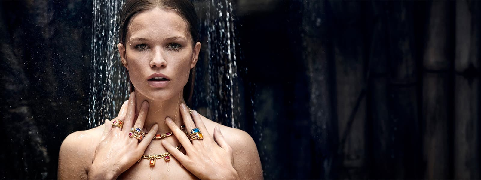 A color photo of model Anna Ewers wearing David Yurman Novella necklaces, gold chains and stacked rings with colored gemstones in an outdoor shower.