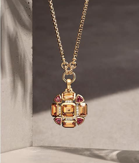 A color photograph of an 18K yellow gold chain necklace with a Novella pendant featuring citrines and pink tourmalines hanging in front of a stone background with shadows of leaves.