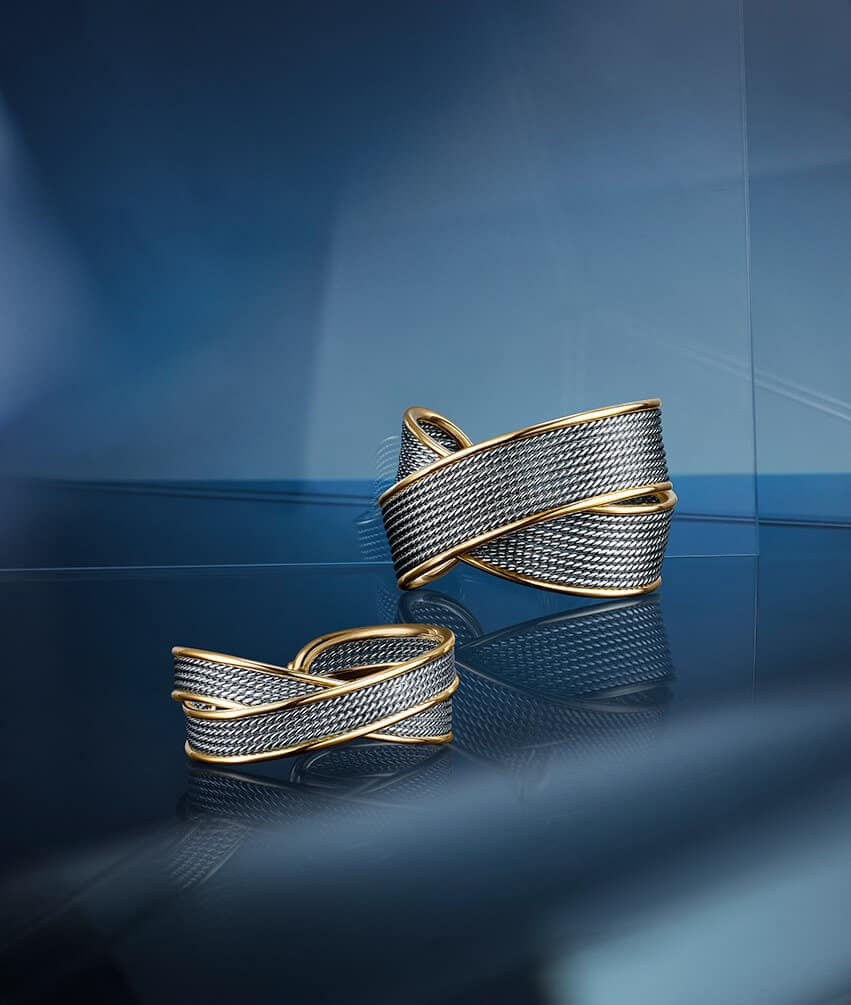 Two color photos of DY Origami jewelry shot on a dark blue background are placed side by side. The photo on the left shows a pair of 18K yellow-gold-and-diamond earrings suspended in the air next to a matching pendant necklace. The image on the right shows a chain link necklace with pavé diamond highlights along the front.