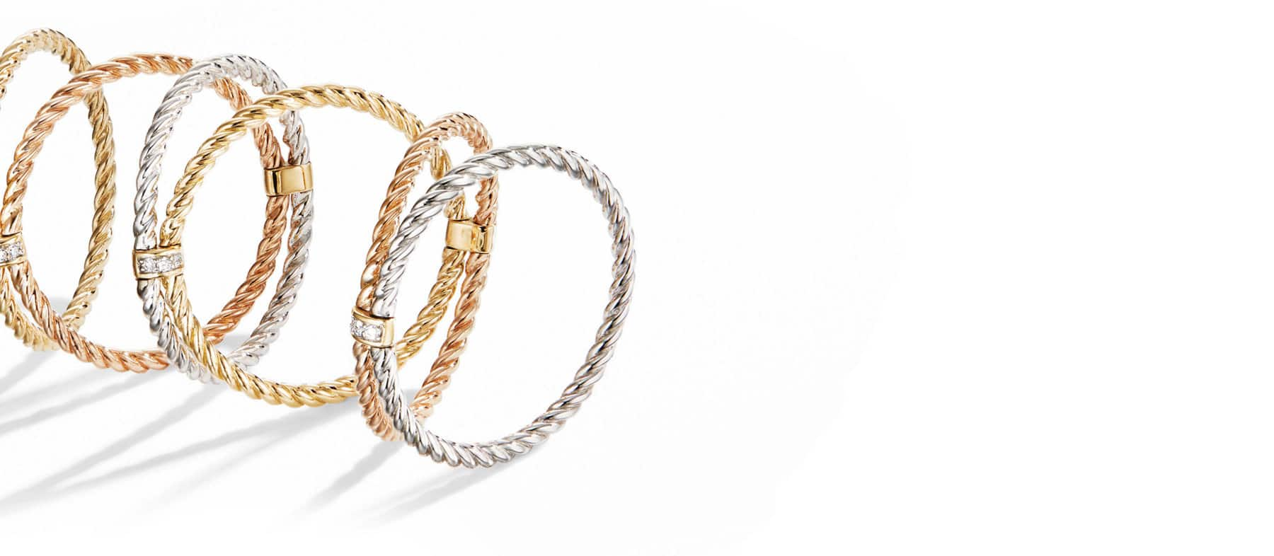 A color photo of our Origami 6 row cable ring in mixed yellow, rose and white gold