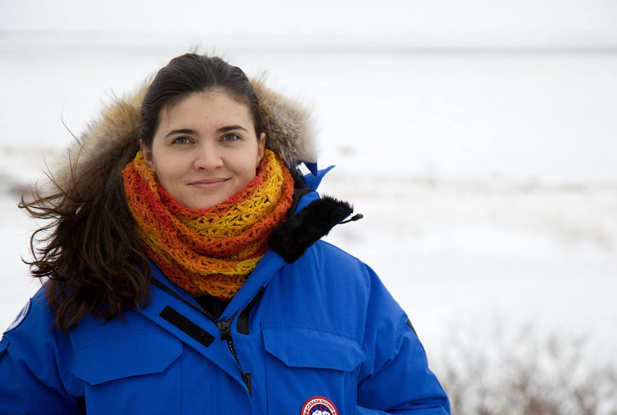 A color photo shows Dr. Thea Bechshoft standing in front of a snow-covered Arctic landscape wearing a blue parka and a red-and-orange scarf.
