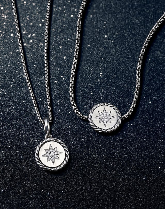An overhead shot shows a David Yurman North Star pendant necklace and bracelet placed on top of a glittery black backdrop. The women's jewelry is crafted from sterling silver and features pavé diamond stars in the center of each charm.